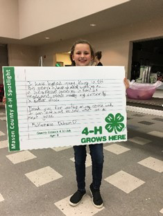 4-H participant holding up poster project